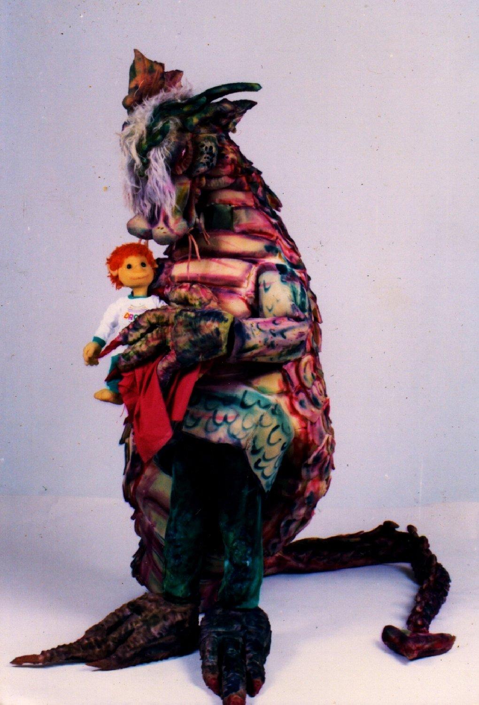Le jeune garçon Menino avec un dragon, dans <em>Na Pontinha do Sonho</em> (1989) par le Grupo Teatro de Bonecos Patati & Patatá and Zero Cia. de Bonecos (Belo Horizonte, Minas Gerais, Brésil), texte, mise en scène, conception, création et manipulation : Grupo Teatro de Bonecos Patati & Patatá and Zero Cia. de Bonecos. Une marionnette en mousse sur table et une marionnette habitable. Photo réproduite avec l'aimable autorisation de Grupo Teatro de Bonecos Patati & Patatá and Zero Cia. de Bonecos