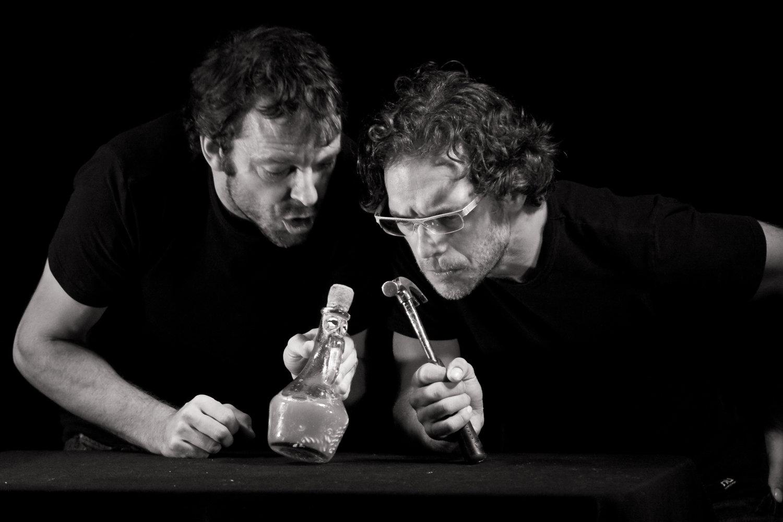 Francis Monty avec Père Ubu (la bouteille) et Olivier Ducas with Captain Bordure (le marteau) dans <em>Ubu sur la table</em> (créé en 1998) par le Théâtre de la Pire-Espèce, adapté de <em>Ubu roi</em> d'Alfred Jarry, mise en scène : Olivier Ducas et Francis Monty. Photo: Djeyo