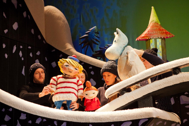 <em>Moominland Midwinter</em> (2013) par le Horse + Bamboo Theatre (Rossendale, Angleterre), une coproduction avec The egg (Bath, Angleterre), mise en scène : Lee Lyford et Alison Duddle, scénographie: Tom Rogers, conception et fabrication de marionnettes : Horse + Bamboo. Acteurs sur la photo : Adam Fuller, Morag Cross, Zoe Hunter, Seamas Carey. Marionnettes sur table. Droits des personnages : Moomin Characters Ltd., 2013. Photo réproduite avec l'aimable autorisation de Horse + Bamboo Theatre