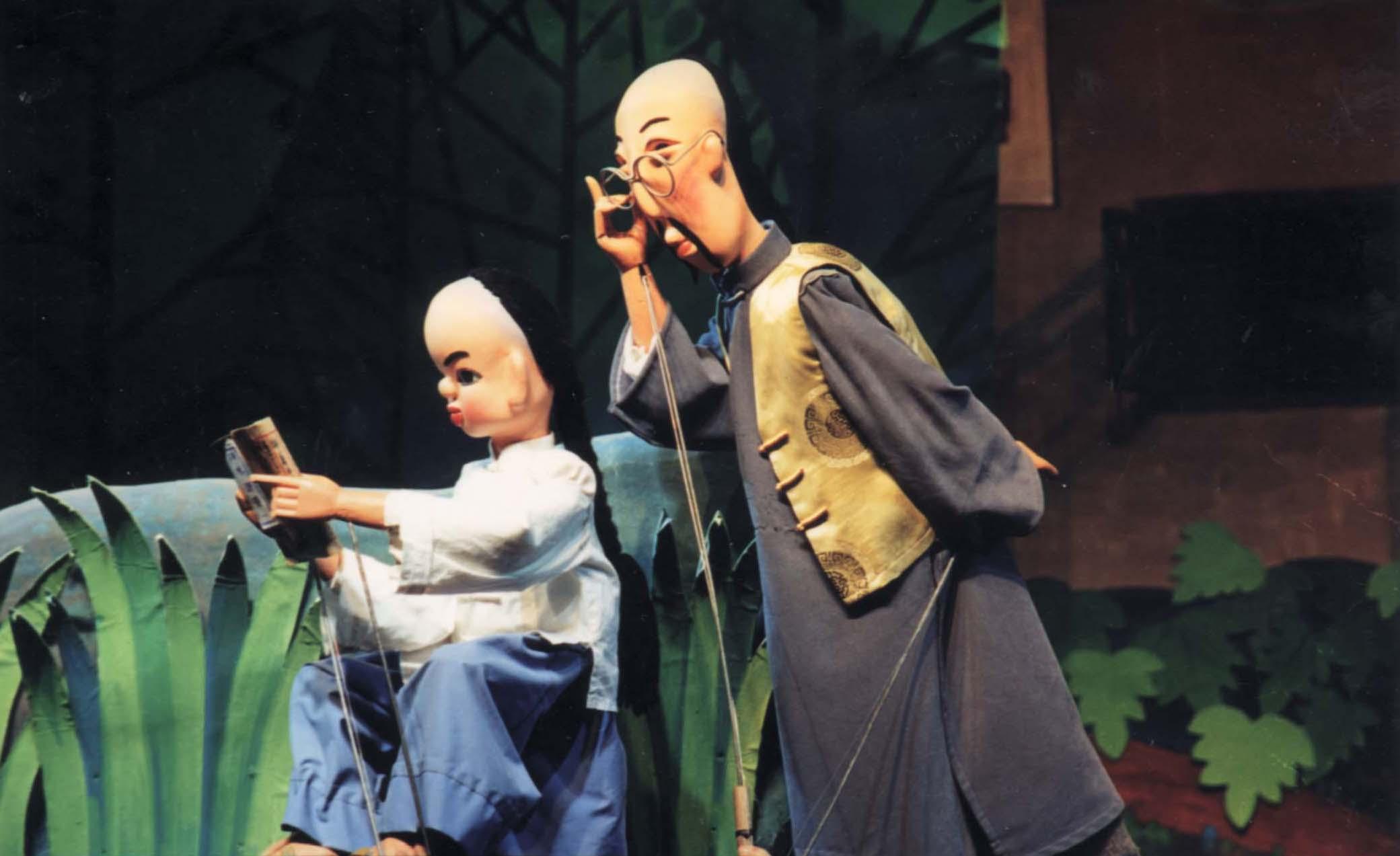 <em>Le garçon, Shi numéro trois</em> (石三伢子, 2003) par Hunansheng Muou Piying Yishu Juyuan (Centre pour la préservation de la marionnette et le théâtre d'ombres, province du Hunan, République populaire de Chine ), mise en scène : Xiong Guo'an, Zhang Jie, scénographieet fabrication: Yi Jianmin, Li Yonghong, marionnettistes : Nie Shiqi, Wang Teran. Marionnettes à tiges. Photo réproduite avec l'aimable autorisation de Hunansheng Muou Piying Yishu Juyuan