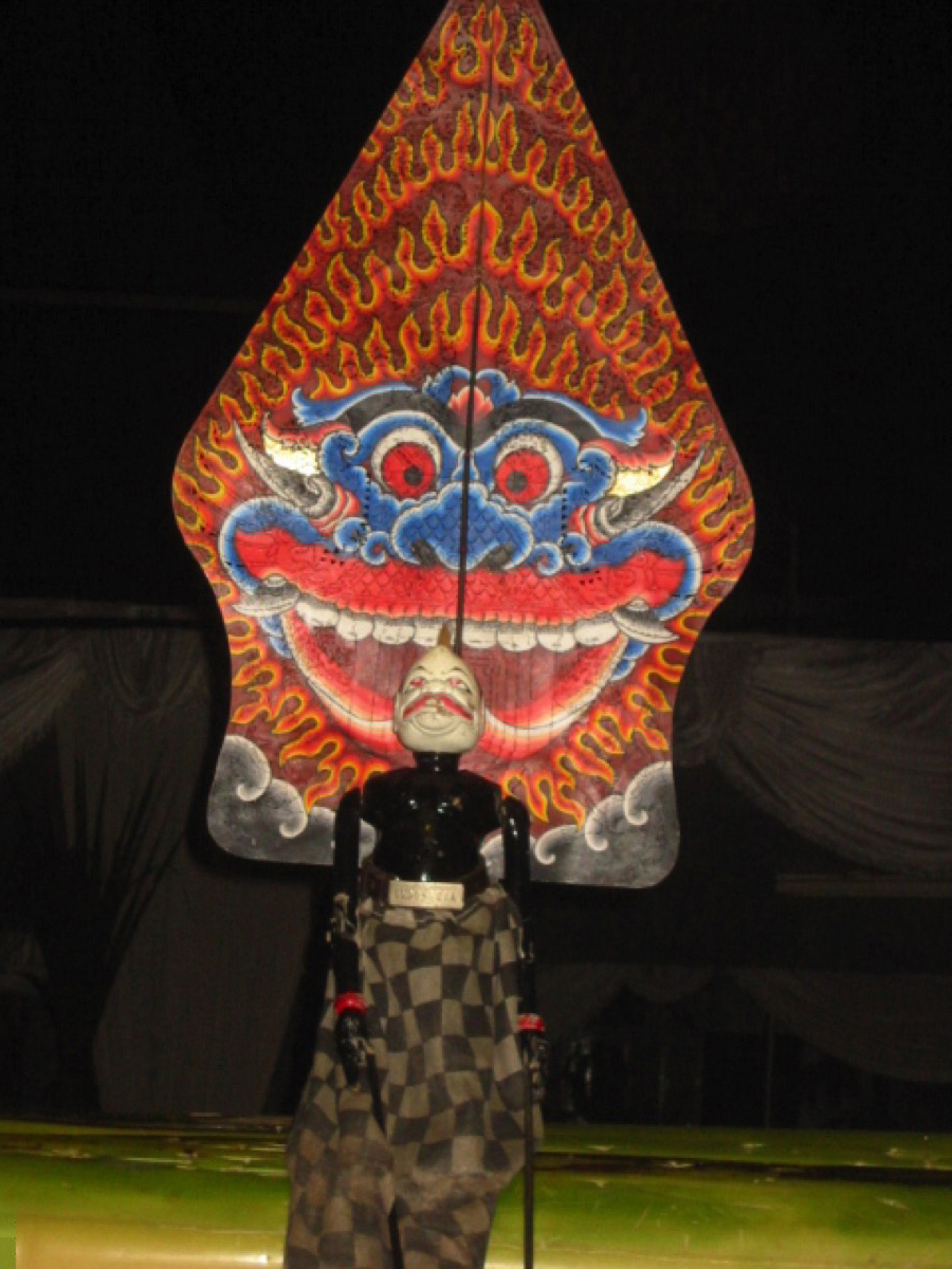 Semar, une marionnette à tiges de <em><em>wayang</em> golek <em>Sunda</em></em> apparaissant devant le flanc de la figurine d'ombre, <em>kayon</em> (<em>gunungan</em>), qui représente le visage de Kala. Photo: Karen Smith