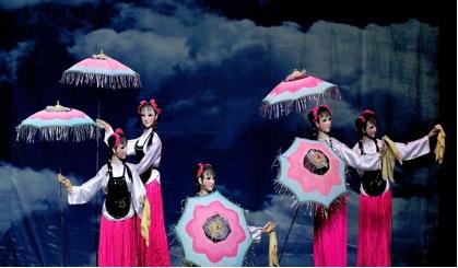 <em>Danse de parapluie fleuri</em> (花伞舞, 1990) par Sichuansheng Damuou Juyuan (Beiqiandao, district de Shunqing, Nanchong, province du Sichuan, République populaire de Chine), mise en scène : Tang Guoliang, Long Lixiao, scénographieet fabrication : Shu Shilin, Zhao Qing, Xu Xueshu, Xian Guanghui, Hu Xingying, marionnettistes : les jeunes artistes de la compagnie. Marionnettes à tiges, hauteur : 1,8-2 m. Photo réproduite avec l'aimable autorisation de Sichuansheng Damuou Juyuan
