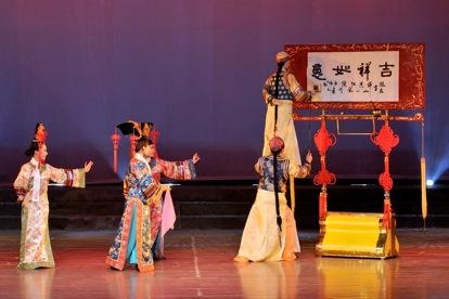 <em>Un grand marionnette écrit la calligraphie</em> (大木偶书艺, 2006) par Sichuansheng Damuou Juyuan (Beiqiandao, district de Shunqing, Nanchong, province du Sichuan, République populaire de Chine), mise en scène : Tang Guoliang, scénographieet fabrication : Shu Shilin, Zhao Qing, Xu Xueshu, Xian Guanghui, Hu Xingying, marionnettiste : Chen Gongtao. Marionnette à tiges, hauteur : 1,8-2 m