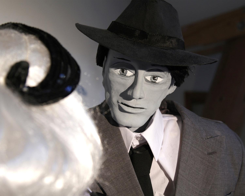 Sam Stone, dans <em>One Way Street</em> (2010) par Small World Theatre (Cardigan, Pays de Galles, Royaume-Uni), un film noir thriller de marionnettes pour les adultes, conception et fabrication: Bill Hamblett (regard extérieur) : Liz Walker, acteurs : Bill Hamblett, Ann Shrosbree, Debbie Woolley, Toby Downing. Hauteur de la marionnette de Sam Stone: 2 m. Théâtre d'ombres, marionnettes à tiges, marionnettes empoignée, multimédia (animation, projection, films d'archives, et son). Une application a été créée pour le spectacle afin que le public puisse devenir un personnage de la pièce. Photo: Sam Vicary