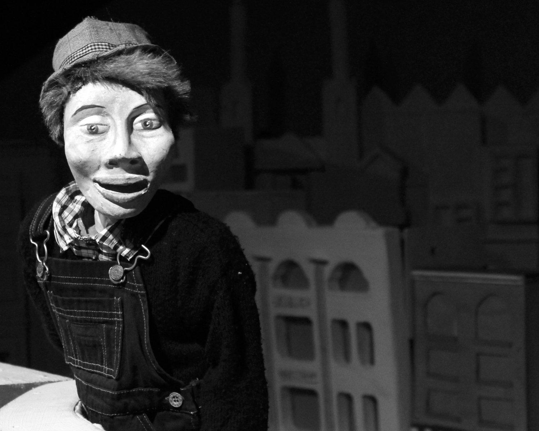 Sidekick Joe, dans <em>One Way Street</em> (2010) par Small World Theatre (Cardigan, Pays de Galles, Royaume-Uni), conception et fabrication: Bill Hamblett, regard extérieur : Liz Walker,  acteurs : Bill Hamblett, Ann Shrosbree, Debbie Woolley, Toby Downing. Sidekick Joe, hauteur : 75 cm. Théâtre d'ombres, marionnettes à tiges, marionnettes empoignée, multimédia (animation, projection, films d'archives, et son). Photo: Sam Vicary