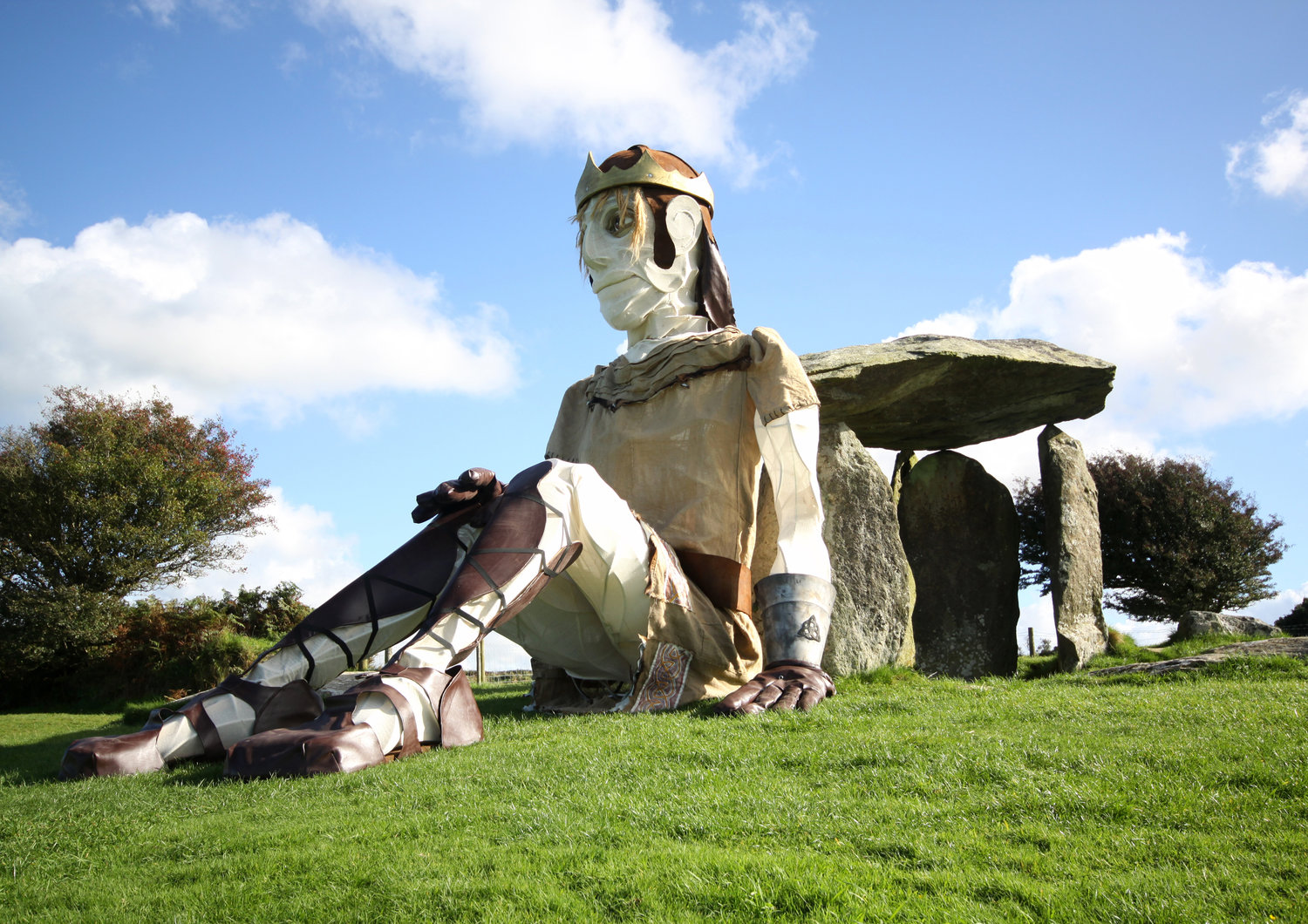 Bendigeidfran (Brân the Blessed) sitting against the Megalithic burial chamber Pentre Ifan (North Pembrokshire, Wales), in <em>The <em>Healing of Brân / Iachau Bendigeidfran</em></em> (2010) by Small World Theatre (Cardigan, Wales, UK). Human-powered giant puppet, height: 7.6 m. An epic outdoor performance based on Welsh folklore and the Tales of the Mabinogion, performed in Welsh and English, with giant puppetry, actors on giant tricycles and a boat, street artists, local choirs, community participation. Photo: Sam Vicary