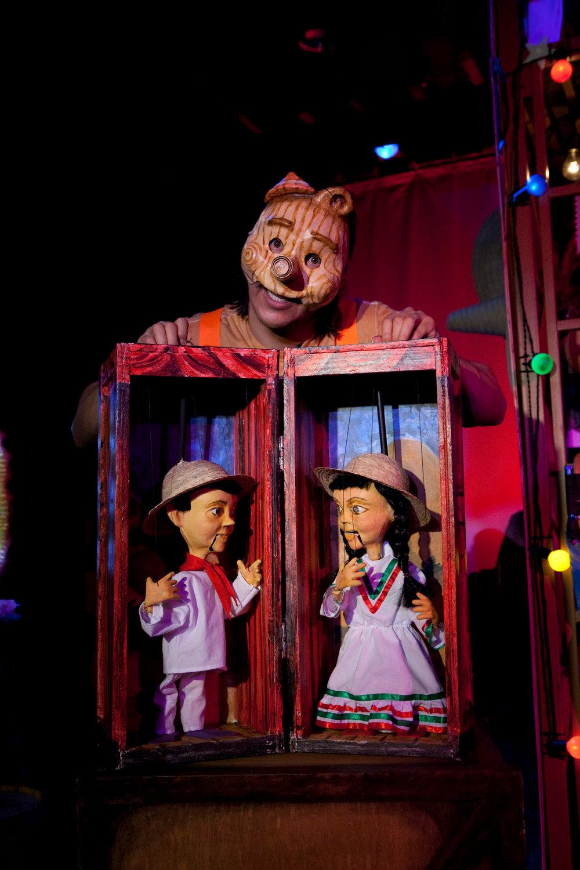 Scène de <em>!Viva Pinocho! A Mexican <em>Pinocchio</em></em>, une production bilingue (anglais et espagnol) pour le jeune public par le Teatro SEA (New York, NY, États-Unis), mise en scène : Manuel Morán, scénographie : José López, musique : Harold Gutiérrez. Marionnettes à fils basées sur les marionnettes mexicaines traditionnelles, hauteur : 46 cm. Marionnettiste / personnage sur la photo : Manuel Morán. Photo: Christopher Auger-Domínguez