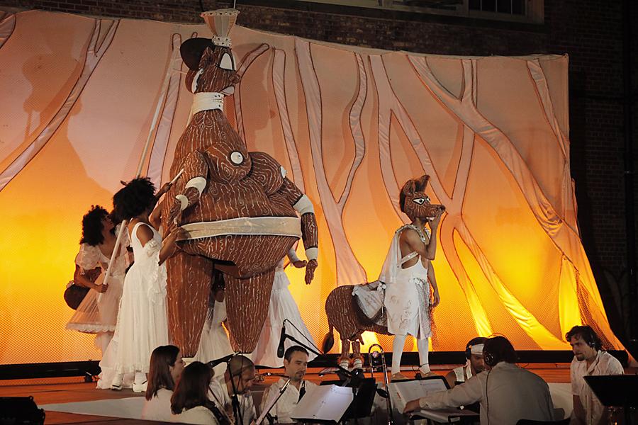 """Titania et Bottom. Scène de Sueño: A Latino Take on Shakespeare's """"Midsummer Night's Dream"""" / Sueño: La Versión Latinizada de """"Sueño de una Noche de Verano"""" de William Skakespeare, une production bilingue (anglais et espagnol) avec les acteurs, chanteurs, musiciens, danseurs, marionnettistes et marionnettes pour un public adulte par le Teatro SEA (New York, NY, États-Unis), mise en scène : Manuel Morán, scénographie et marionnettes : José López. Marionnette à tige géant et marionnette habitable, hauteur : (Titania) 3,7 m, (Bottom) 1,8 m. Photo: Ruiz Photography"""