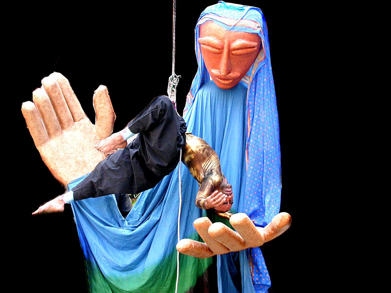 De<em>c</em>ote (2005), la <em>c</em>érémonie d'ouverture du Ishara International Puppet Theatre Festival (New Delhi, Inde), un spe<em>c</em>ta<em>c</em>le spé<em>c</em>ifique au site ave<em>c</em> une grande balan<em>c</em>e aérienne, des danseurs, des marionnettes, des masques et des objets, dirigés, <em>c</em>horégraphiés et réalisés par Sudesh Adhana. Con<em>c</em>eption de marionnettes : Dadi Pudumjee, <em>c</em>onstru<em>c</em>tion de marionnettes : Dadi Pudumjee et membres d'Ishara. Marionnettistes sur la photo : Dadi Pudumjee, manipulant la marionnette géante, ave<em>c</em> les marionnettistes d'Ishara, et la danseur exé<em>c</em>utant le travail de la <em>c</em>orde. Marionnette à tiges géantes, hauteur : env. 3,60 m. Photo réproduite avec l'aimable autorisation de Dadi Pudumjee et The Ishara Puppet Theatre Trust