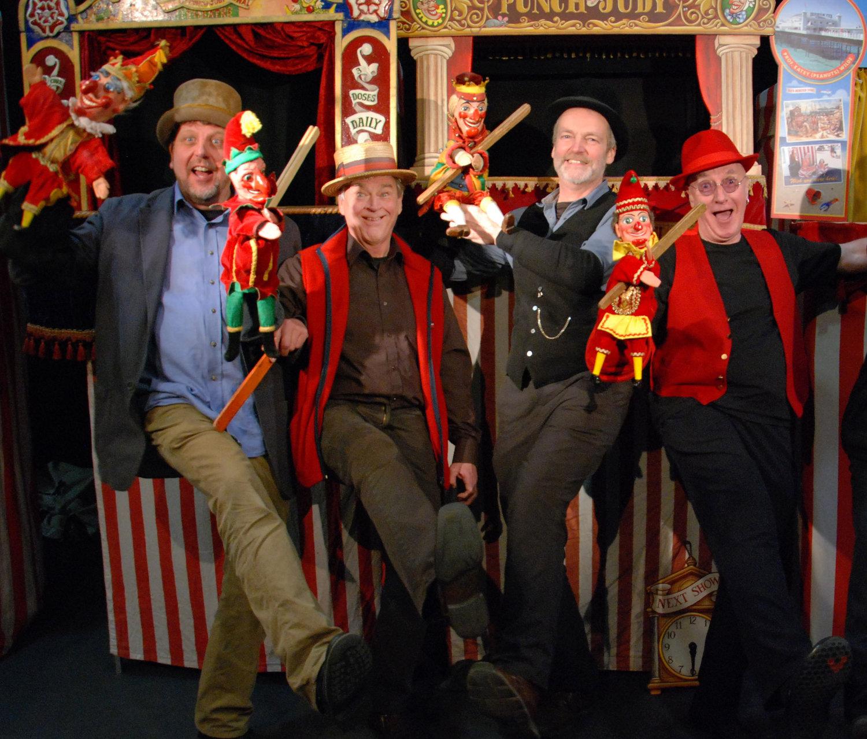 Quatre « Professors » du <em>Pun<em>c</em>h and Judy</em> College of Professors, <em>c</em>ha<em>c</em>un ave<em>c</em> leur Pun<em>c</em>h en main, leur meilleur pied en avant (mai 2012). Photo réproduite avec l'aimable autorisation de Glyn Edwards