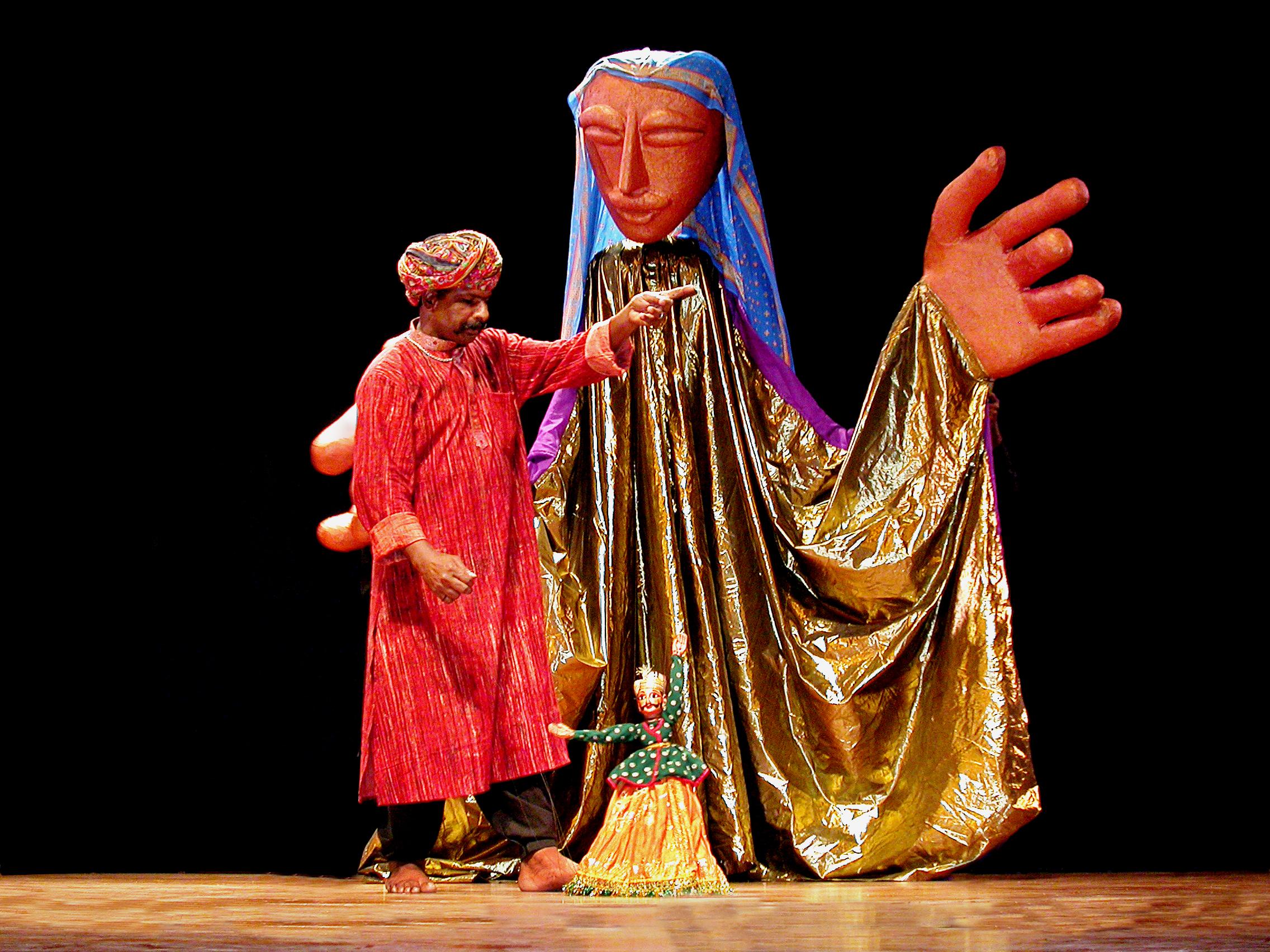 Puran Bhatt, maître marionnettiste du Rajasthan et récipiendaire du Sangeet Natak Akademi Award pour la Marionnette en 2003, manipulant son kathputli behrupia, hauteur : env. 55 cm, pour l'acte d'ouverture par The Ishara Puppet Theatre au festival Sangeet Natak Akademi (New Delhi, début des années 1990)