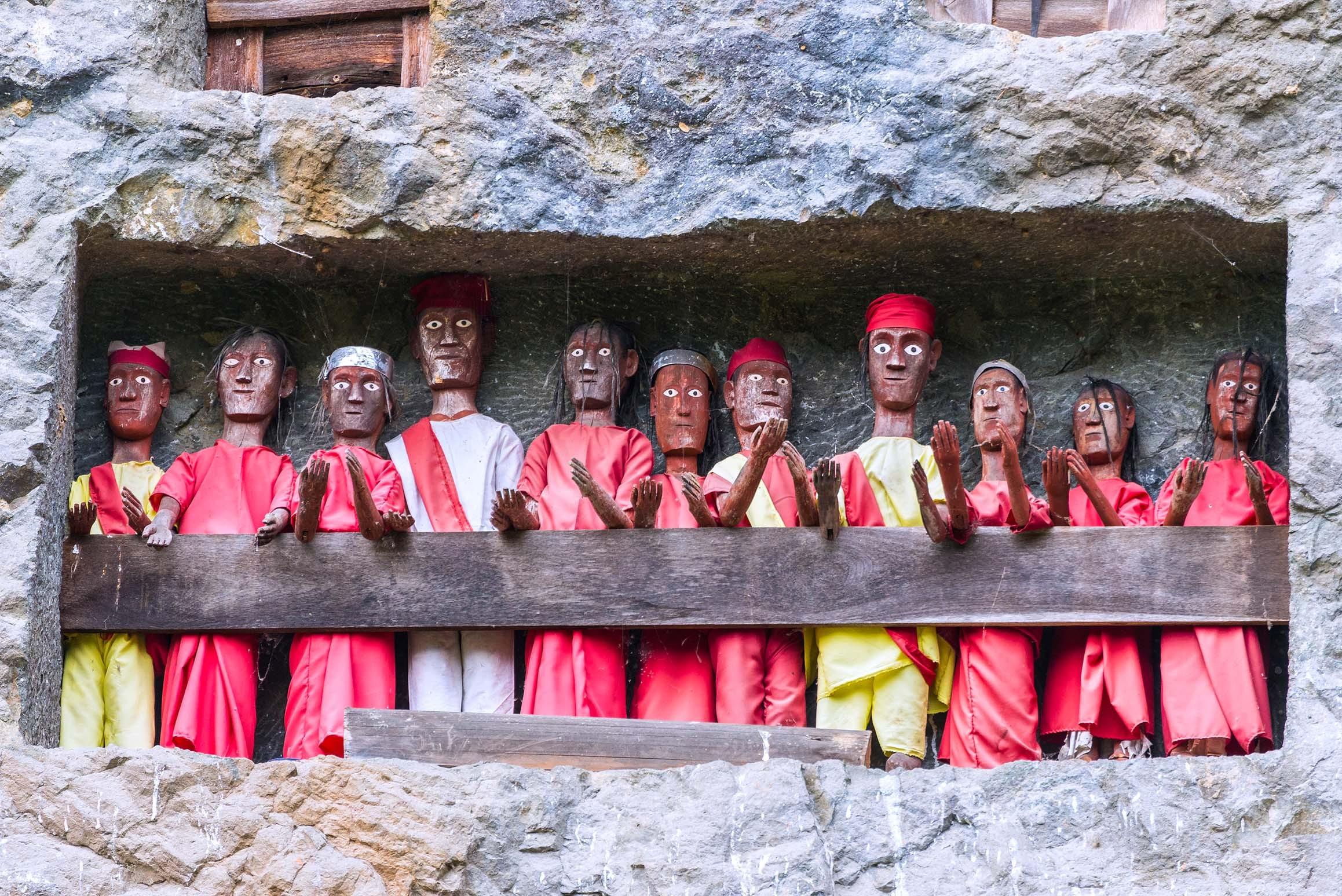 Tau-Tau en bois, des effigies des proches décédés, gardant des tombes sculptées dans des faces verticales de calcaire (Tana Toraja, Sulawesi, Indonésie). Source : http://www.indonesia.travel/en/destination/point-of-interest/<em>tau-tau</em>-statues