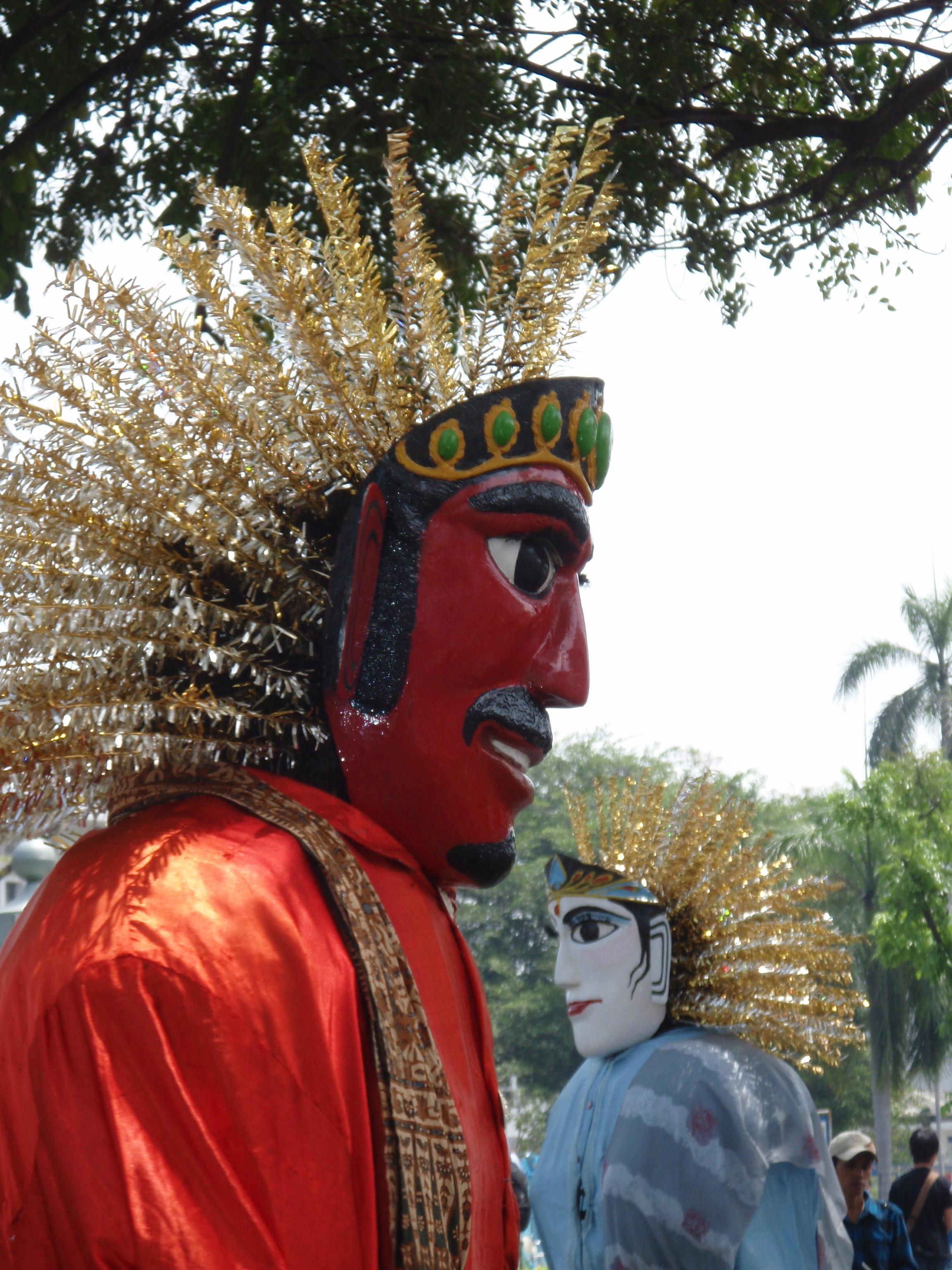 Ondel-ondel, une forme de spectacle folklorique, souvent joués dans des festivals, originaire de Betawi (Jakarta) utilisant de grandes marionnettes, traditionnellement pour protéger contre les calamités ou pour empêcher les esprits malveillants errants. Les variations de ces marionnettes géantes : à Pasundan, les marionnettes sont connues sous le nom de <em>Badawang</em> ; dans le Java central comme Barongan Buncis ; à Bali, <em>Barong Landung</em>. Marionnettes habitables betawi (un mâle, avec le visage peint en rouge, et une femme, avec le visage peint en blanc) en bambou tissé et en tissu, le visage de masque généralement en bois, les cheveux de feuilles de palmier séchées, et portés par une personne, hauteur : environ. 2,50 m, diamètre: env . 80 cm.