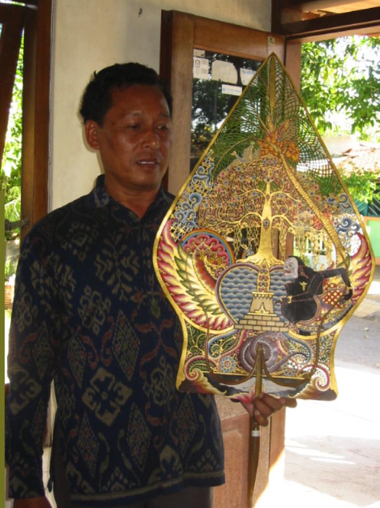 Le <em>dalang</em> javanais, <em>Ki</em> Bambang Suwarno, avec le gunungan (<em>kayon</em>), qu'il a créé représentant Semar méditant sur un lieu sacré (Surakarta, Indonésie).