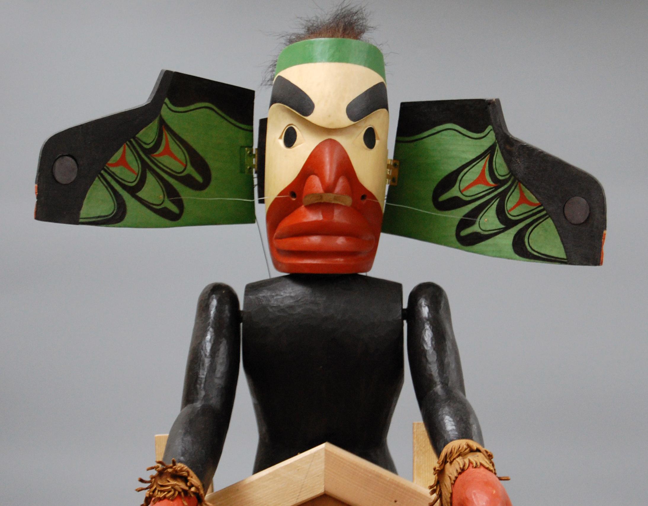 Marionnette à tiges de métamorphose d'un corbeau par George David, un membre des Nuu-chah-nulth / Nuučaan̓uł (Côte Nord-Ouest du Pacifique au Canada). La tête s'ouvre pour révéler les ailes du corbeau