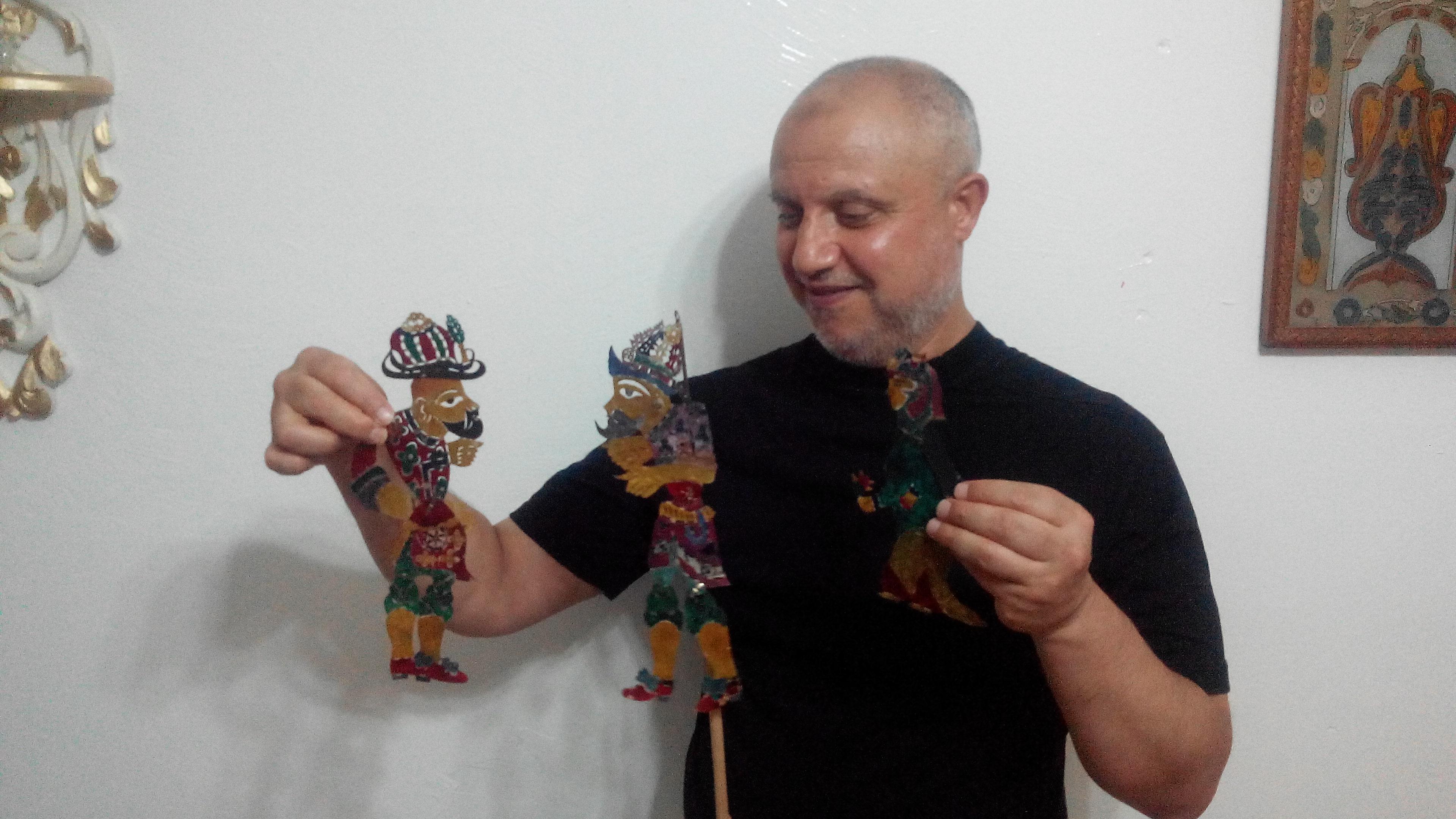 Mohamed Bechir Jaled avec trois de ses marionnettes d'ombre karagouz, fabriqué en 1980. Marionnettes d'ombre en cuir de chèvre avec les tiges métallique, hauteur : 20 cm